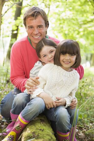 Father and daughters outdoors in woods sitting on log smiling photo