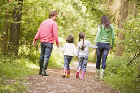 woodland path: Family walking on path holding hands Stock Photo