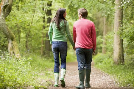 Couple walking on path holding hands photo