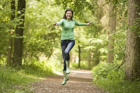 Woman jumping on path smiling photo