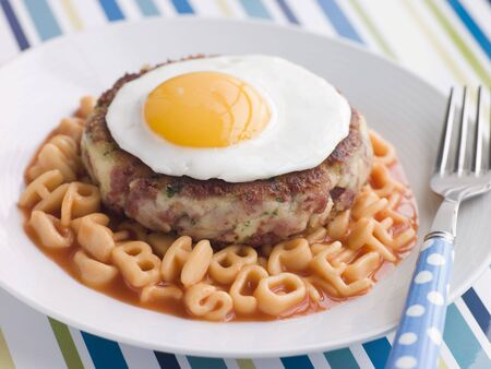 childrens meal: Corned Beef Hash Cake with Alphabet Pasta and a Fried Egg Stock Photo