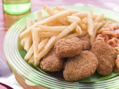 Chicken Nuggets: Trocitos de pollo con espagueti y aros de chips  Foto de archivo