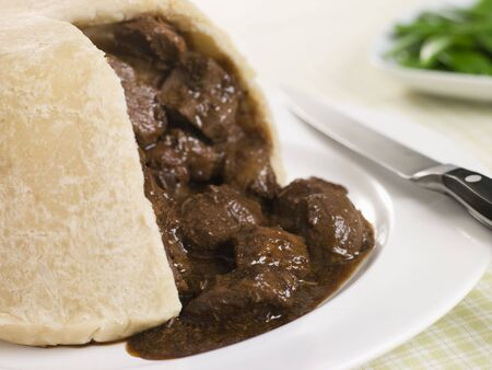 uk cuisine: Steamed Steak and Kidney Pudding with Green Beans Stock Photo