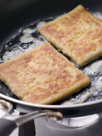 uk cuisine: Potato Farls Frying in Butter Stock Photo
