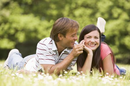 Couple lying outdoors with flower smiling photo