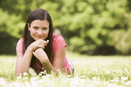 Woman lying outdoors with flower smiling photo