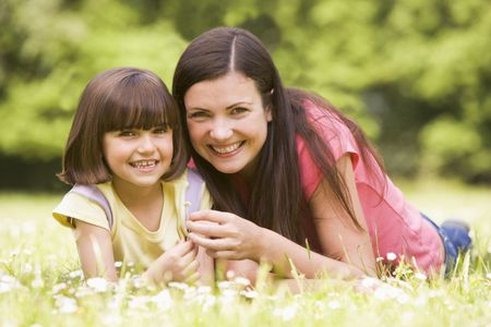 Mother and daughter lying outdoors with flower smiling photo