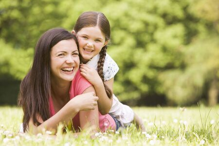 Mother and daughter lying outdoors smiling photo