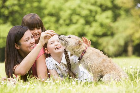 wild dog: Mother and daughters in park with dog smiling Stock Photo