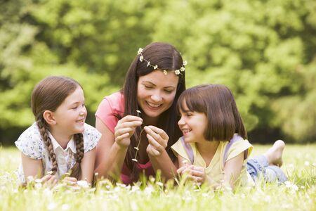 Mother and daughters lying outdoors with flowers smiling photo