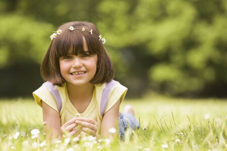 Young girl lying outdoors with flowers smiling photo