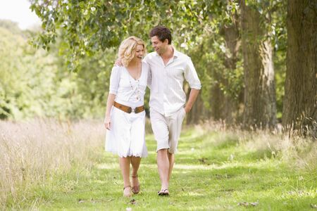 Couple walking on path smiling photo