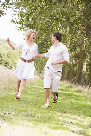 Couple running on path holding hands and smiling photo