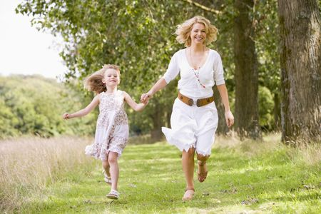 young woman running: Mother and daughter walking on path holding hands smiling