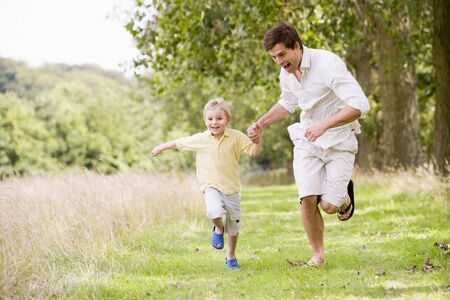 Father and son running on path holding hands smiling Stock Photo - 3600375