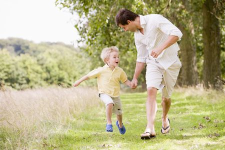 father and son holding hands: Father and son running on path holding hands smiling