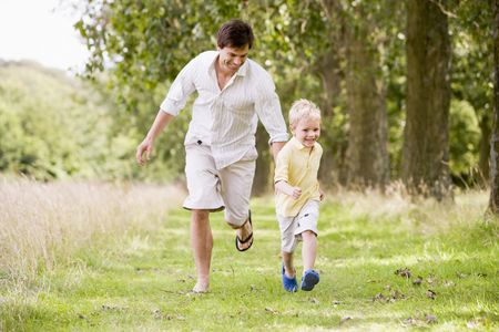 Father and son running on path smiling Stock Photo - 3600404