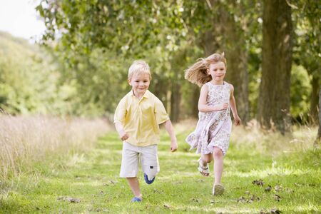 woodland path: Two young children running on path smiling