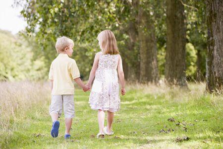 hermanos jugando: Dos ni�os peque�os en la ruta para caminar tomados de la mano