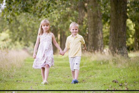ni�os caminando: Dos ni�os peque�os en la ruta para caminar tomados de la mano sonriendo