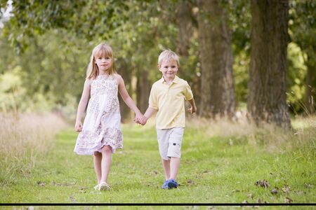 Two young children walking on path holding hands smiling photo