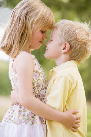 Two young children hugging outdoors photo