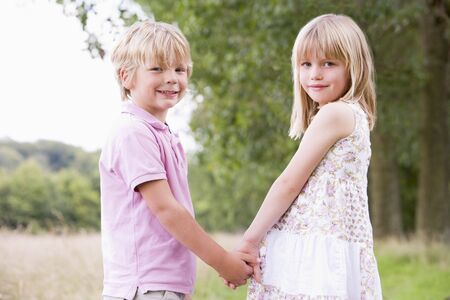 boy and girl holding hands: Two young children standing outdoors holding hands smiling