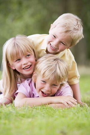 Three young children playing outdoors smiling photo
