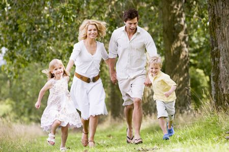 Family running on path holding hands smiling photo
