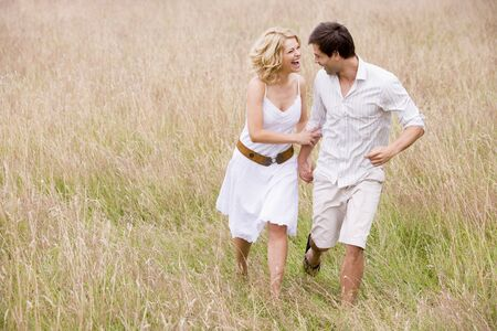 Couple walking outdoors holding hands smiling Stock Photo - 3600446