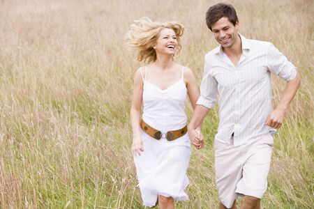 countryside loving: Couple running outdoors holding hands smiling Stock Photo