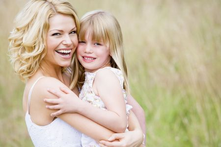 Mother holding daughter outdoors smiling photo