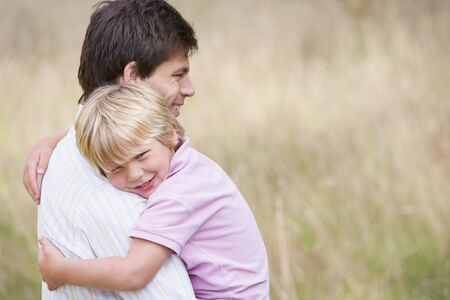 Father holding son outdoors smiling photo
