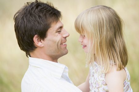 Father holding daughter outdoors smiling Stock Photo - 3600108