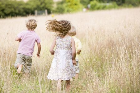 children playing outside: Three young children running outdoors Stock Photo