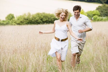 countryside loving: Couple running outdoors smiling