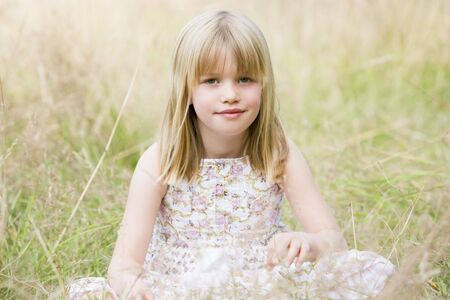Young girl sitting outdoors smiling photo