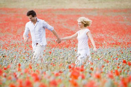 Couple walking in poppy field holding hands smiling Stock Photo