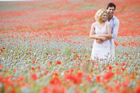 Couple in poppy field embracing and smiling photo