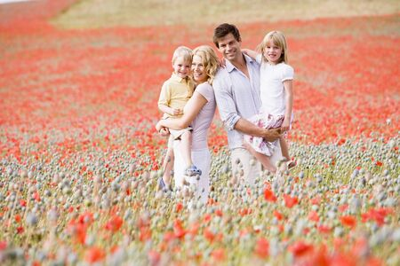 Family standing in poppy field smiling photo