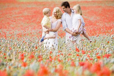 Family standing in poppy field smiling Stock Photo - 3600374