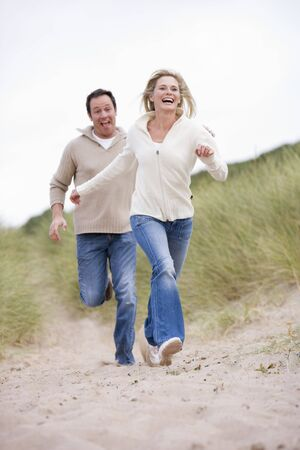 offset angle: Couple running at beach smiling Stock Photo