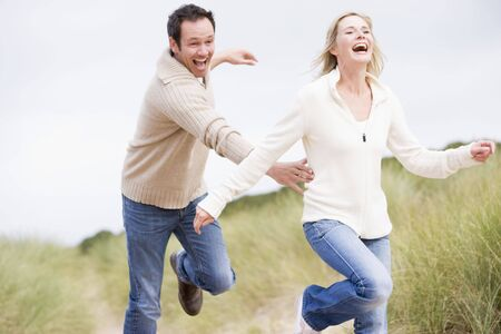 offset view: Couple running at beach smiling Stock Photo