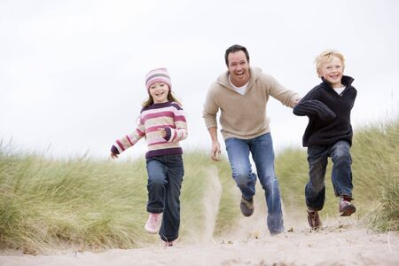 Father and two young children running at beach smiling photo