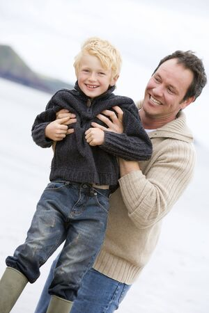 winter escape: Father holding son at beach smiling