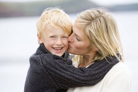 Mother kissing son at beach smiling Stock Photo - 3600355