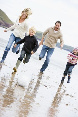 beach clothes: Family playing soccer at beach smiling Stock Photo