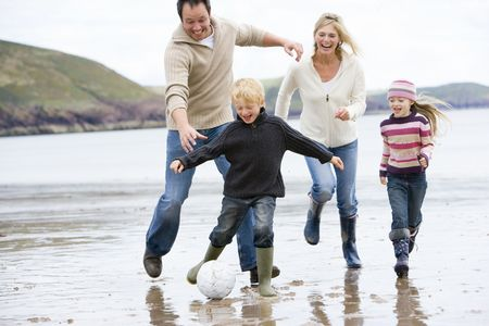 children playing outside: Family playing soccer at beach smiling Stock Photo