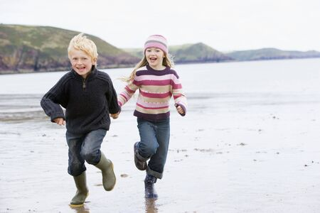 Two young children running on beach holding hands smiling photo
