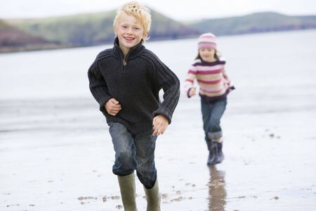 comfy: Two young children running on beach smiling Stock Photo